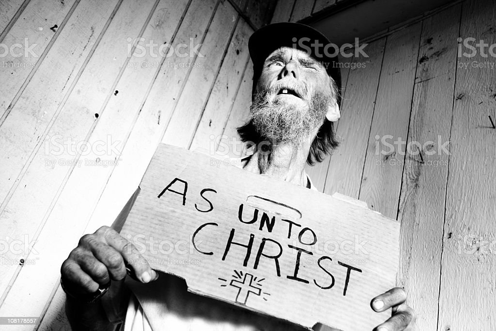 Portrait of Weathered Homeless Man Holding Sign about Christ royalty-free stock photo