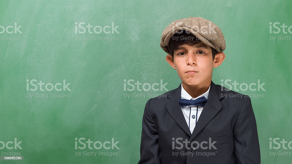 Portrait of well dressed little schoolboy posing in classroom stock photo