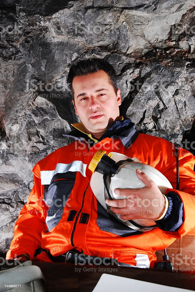 Portrait of white mine worker in an orange uniform in a mine royalty-free stock photo