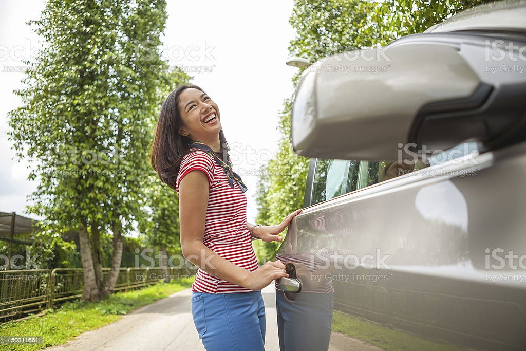 Portrait of woman about to open car door stock photo