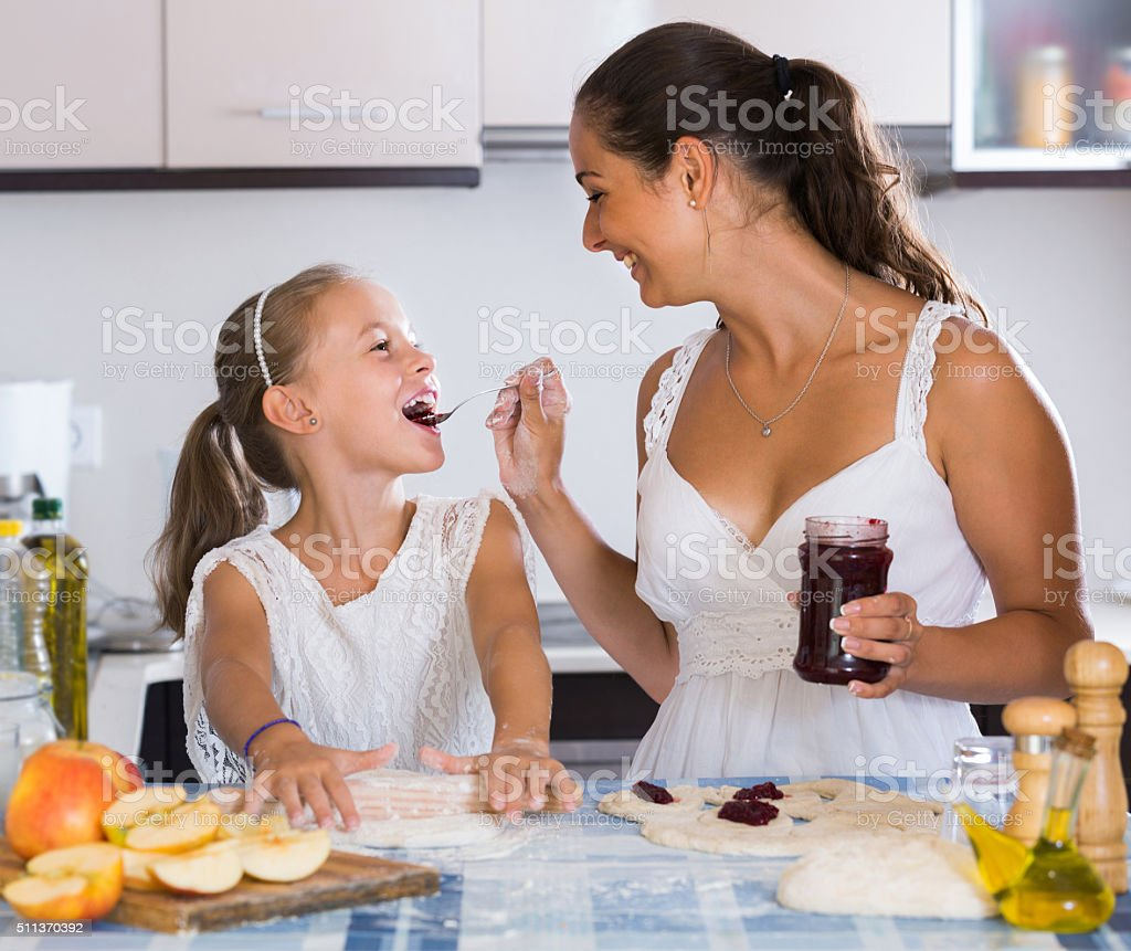 Portrait of  woman and child cooking sweet pies stock photo