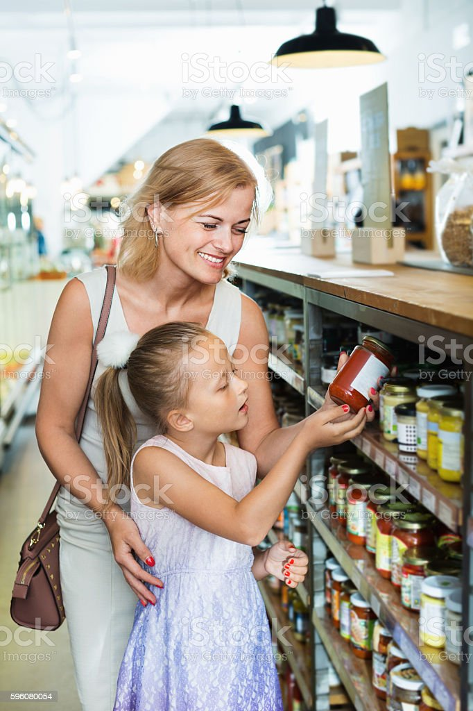 Portrait of  woman and girl buying conserve tomato sauce stock photo