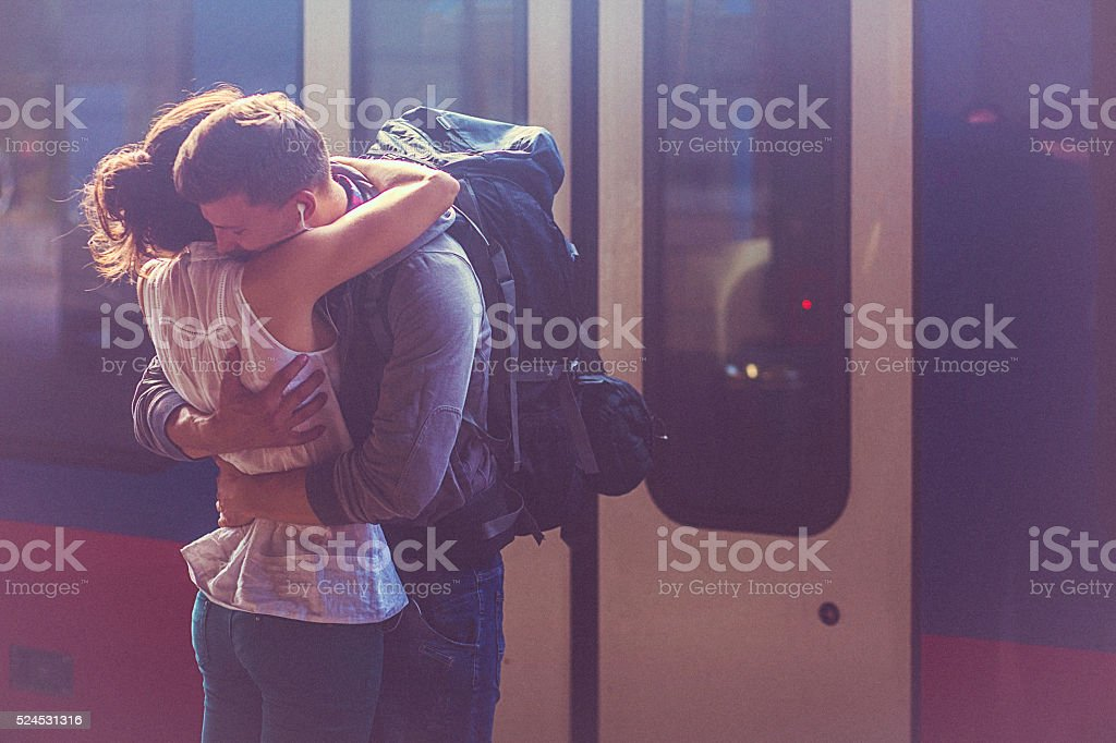 Portrait of woman and man embracing at the railway platform stock photo
