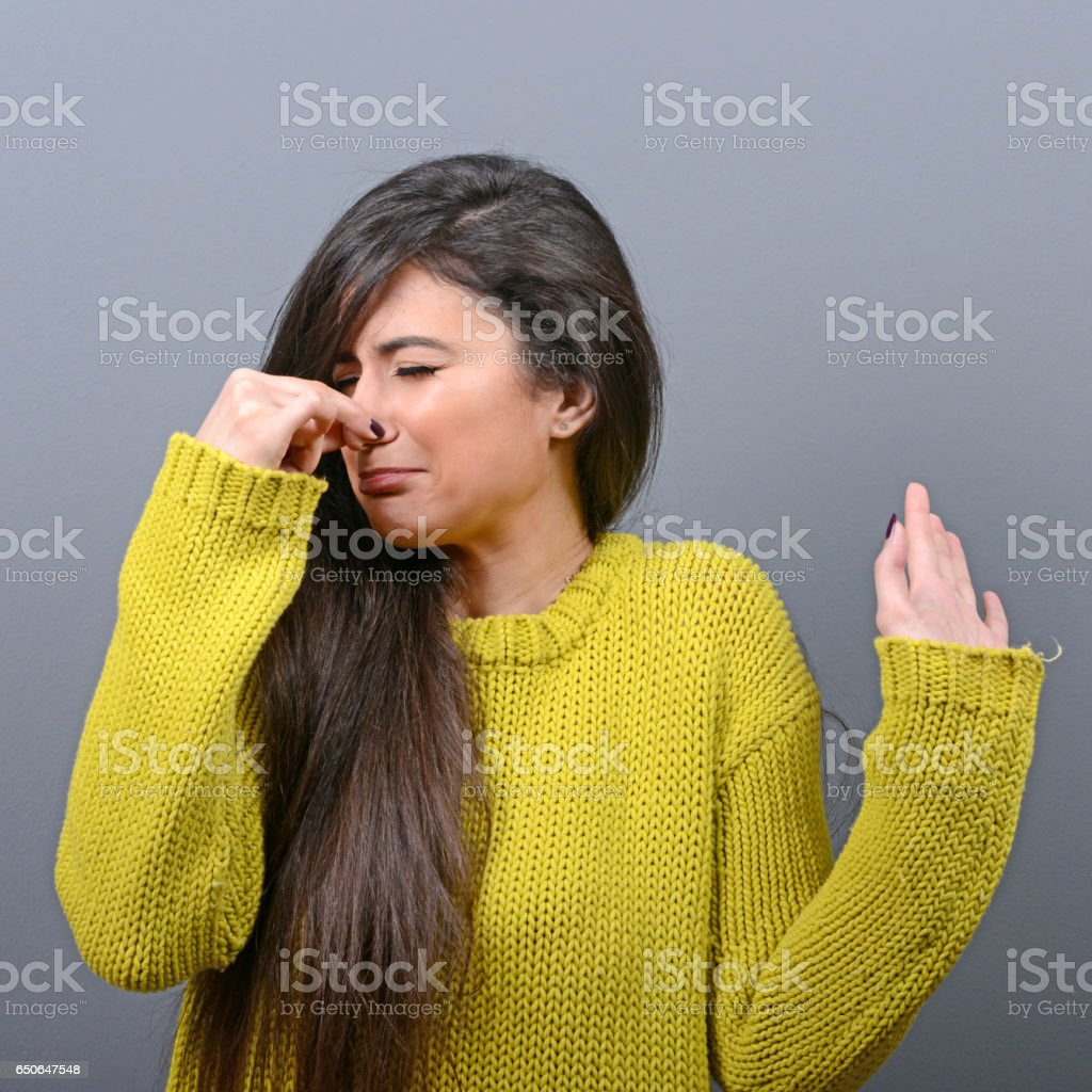 Portrait of woman covering nose with hand showing that something stinks against gray background stock photo