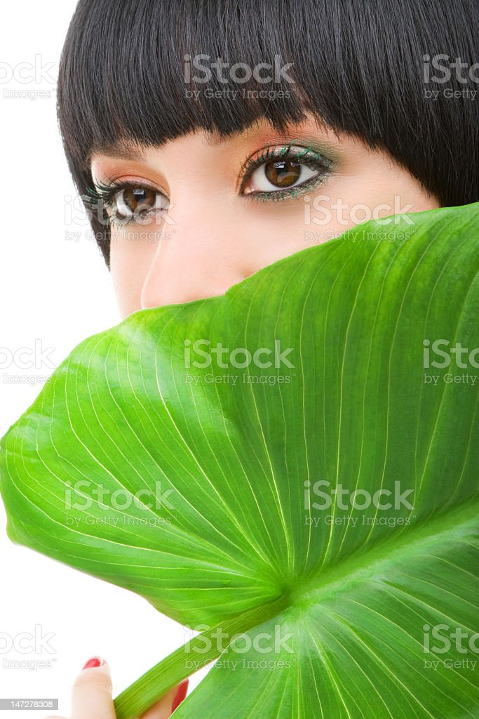 Portrait of woman hiding half her face on a palm leave royalty-free stock photo