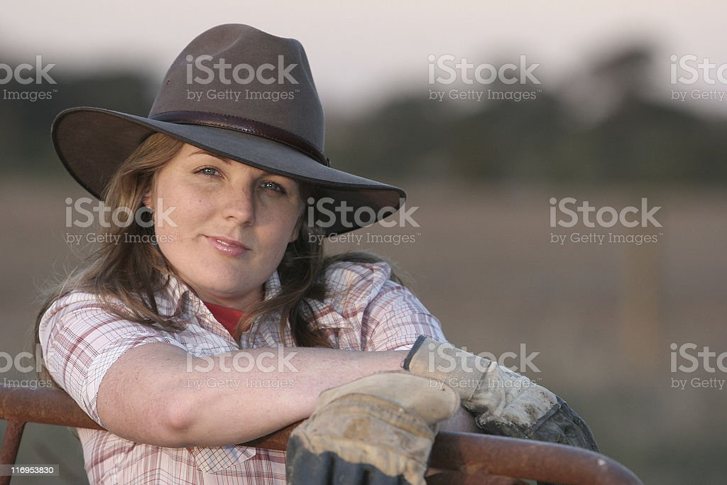 Portrait of woman in a cowboy hat and gloves by an iron gate stock photo