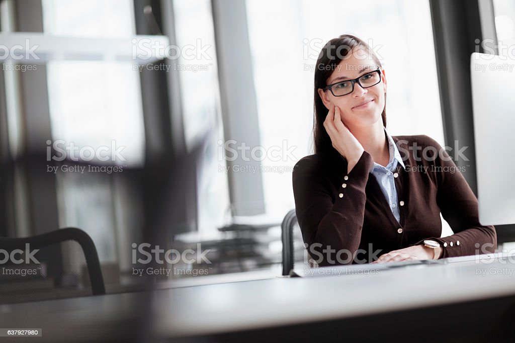 Portrait of woman in modern office setting stock photo