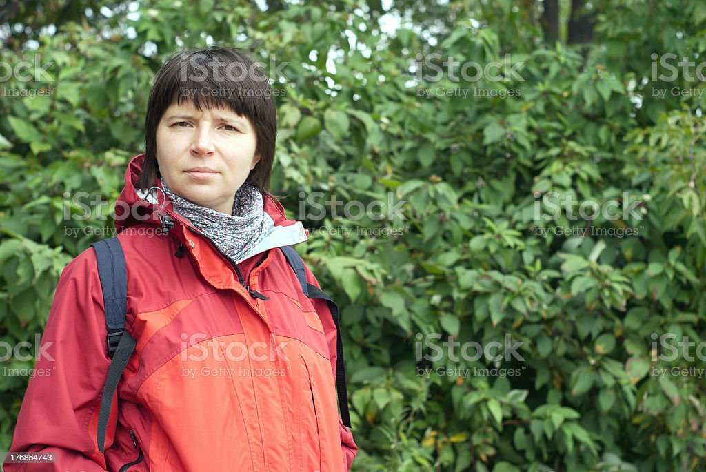 Portrait of woman in red blazer with backpack on nature stock photo