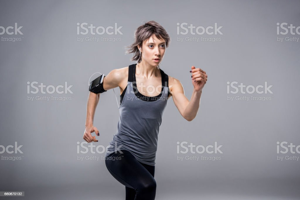 portrait of woman in sportive clothing running in earphones on grey stock photo