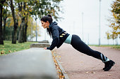 Portrait of woman in sportswear, doing fitness push-ups exercise
