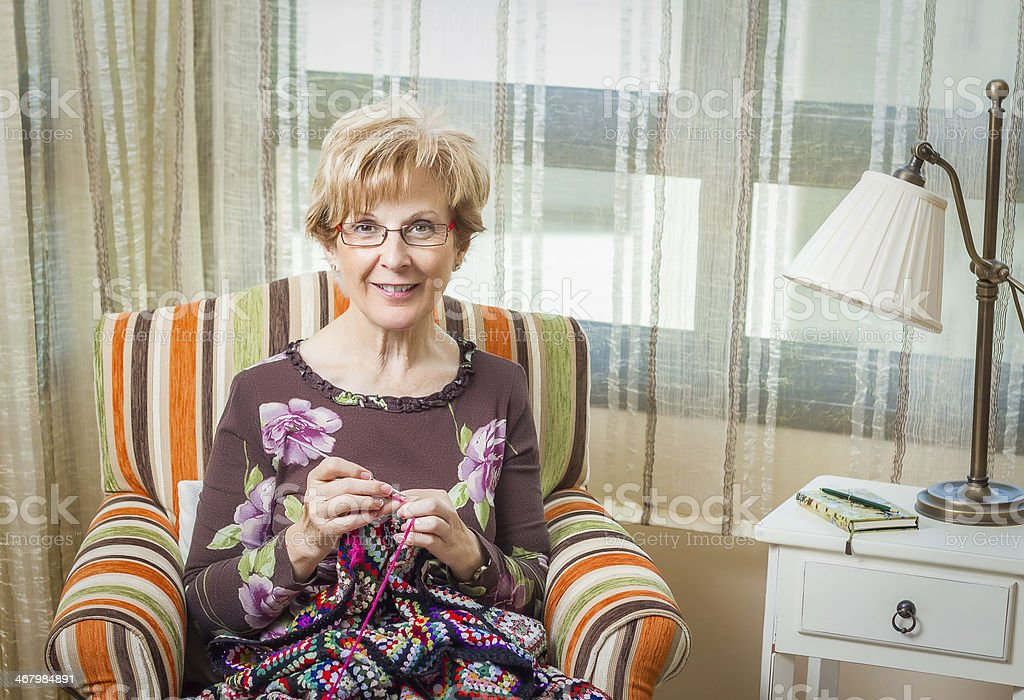 Portrait of woman knitting a vintage wool quilt stock photo