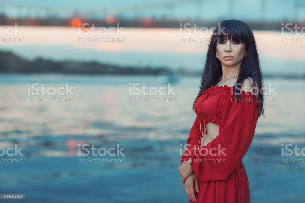 Portrait of woman on a river bank at sunset. stock photo