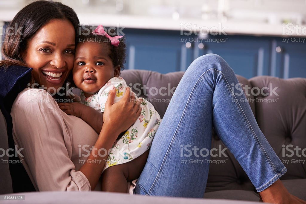 Portrait of woman relaxing at home with her toddler daughter stock photo