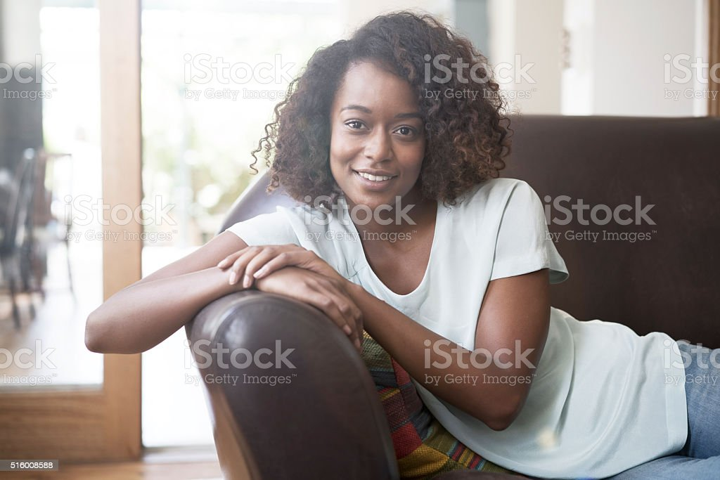 Portrait of woman resting on sofa at home stock photo