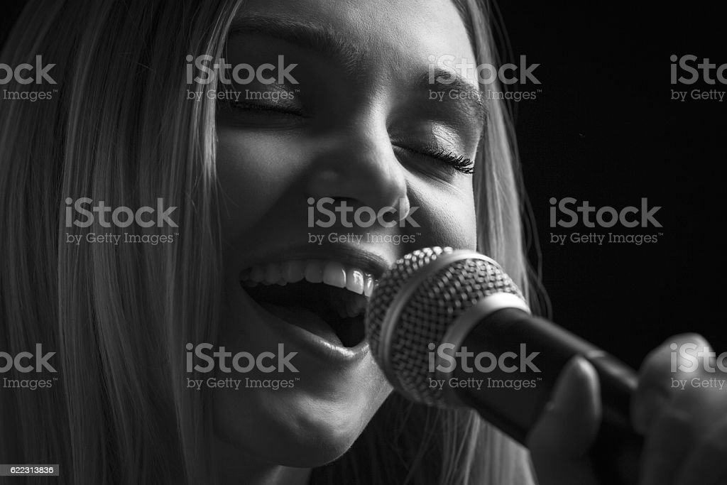 portrait of woman singing into the microphone song stock photo