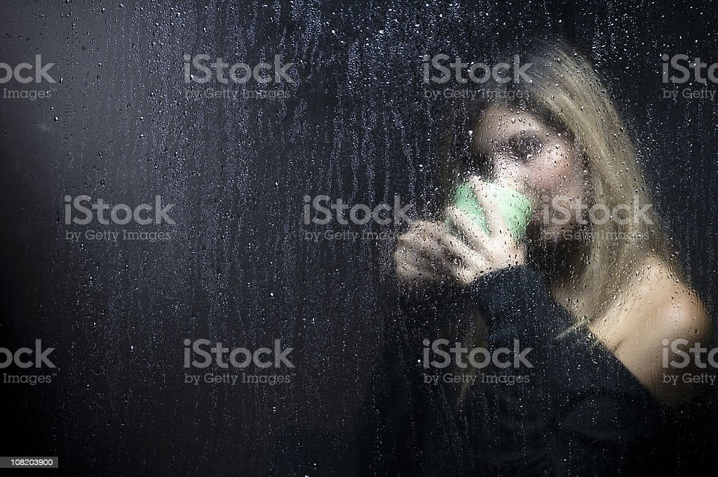 Portrait of Woman Sipping Cup Behind Wet  Window royalty-free stock photo