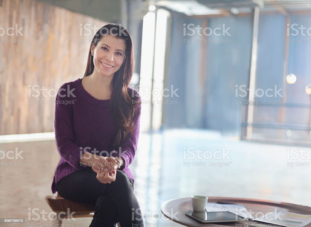 Portrait of woman sitting in large open office studio environment stock photo