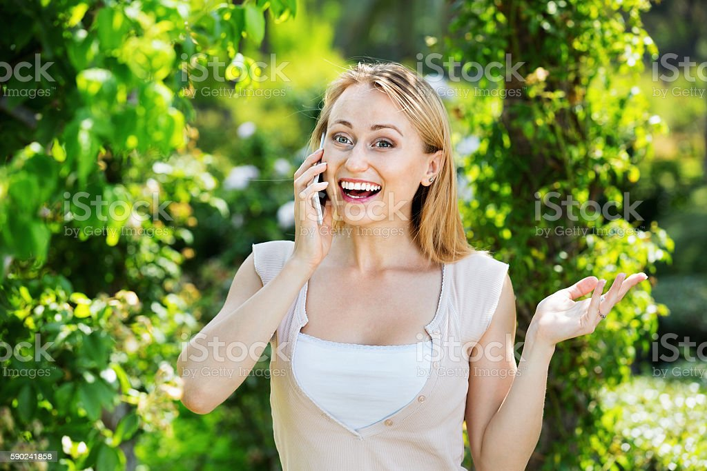Portrait of woman speaking on mobile phone on summer day stock photo