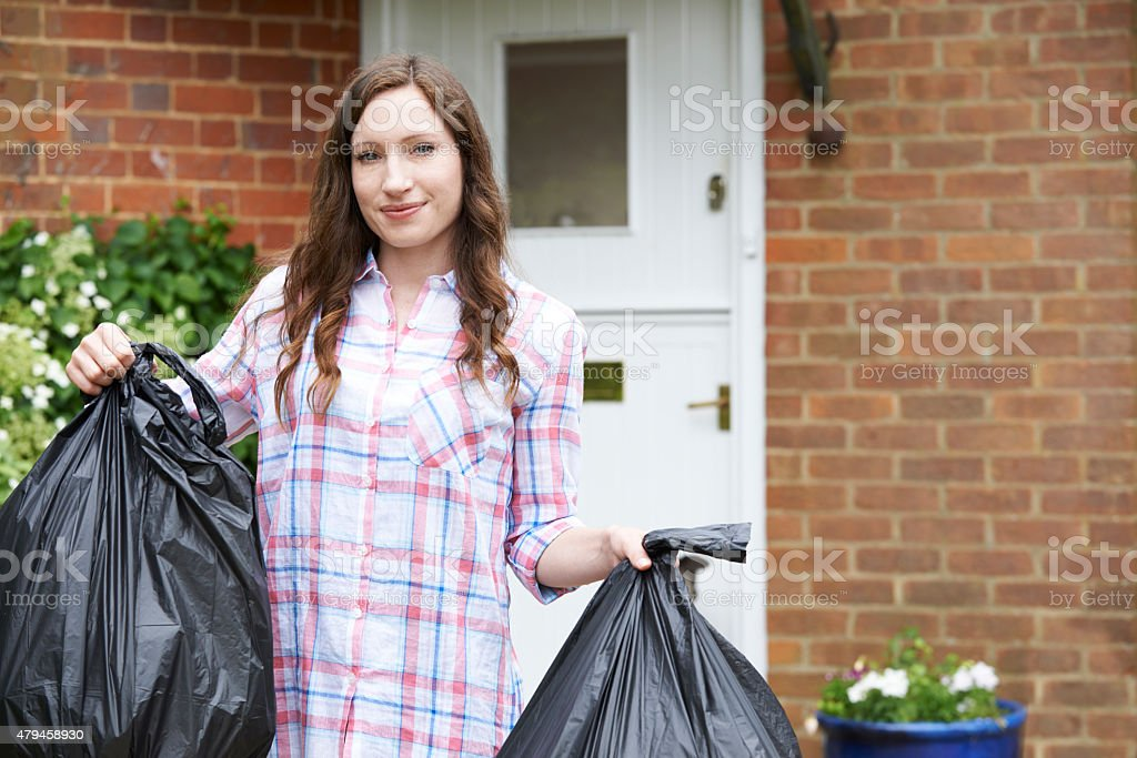 Portrait Of Woman Taking Out Garbage In Bags stock photo