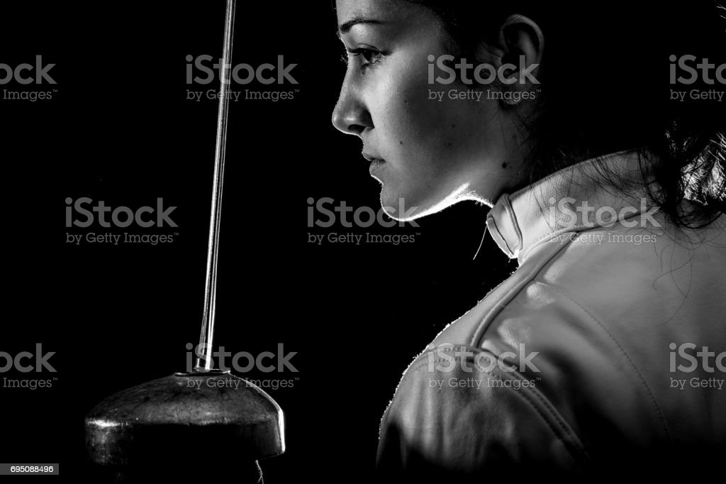 Portrait of woman wearing white fencing costume practicing with the sword.Portrait of woman wearing white fencing costume practicing with the sword. stock photo