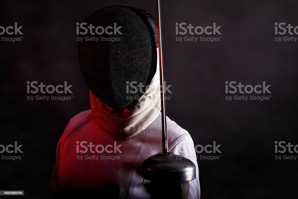 Portrait of woman wearing white fencing costume practicing with the sword. stock photo