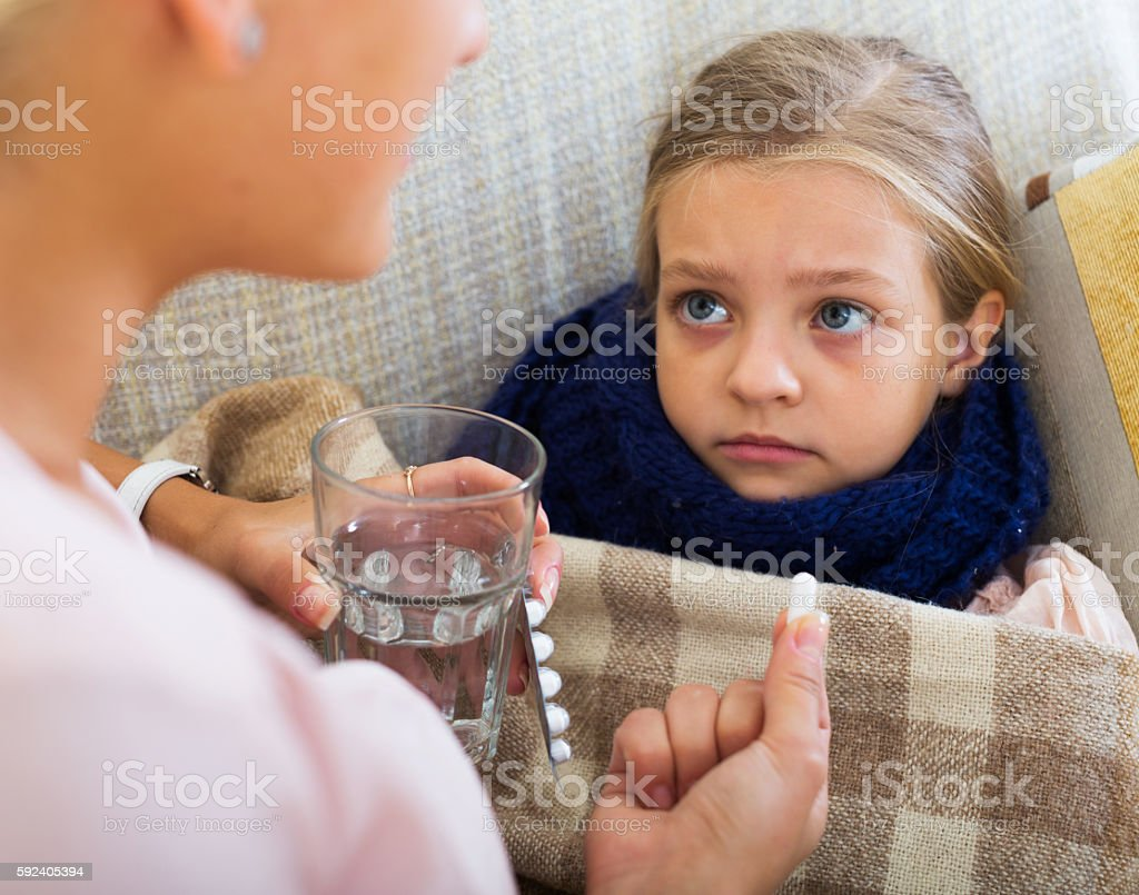 Portrait of woman with antibiotic and child having flu stock photo
