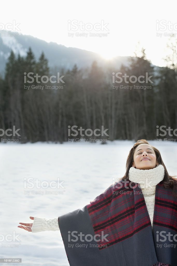 Portrait of woman with head back and arms outstretched in snowy field royalty-free stock photo