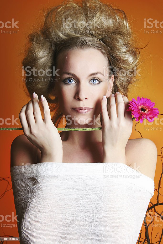 Portrait of Woman Wrapped Up and Holding Flower stock photo