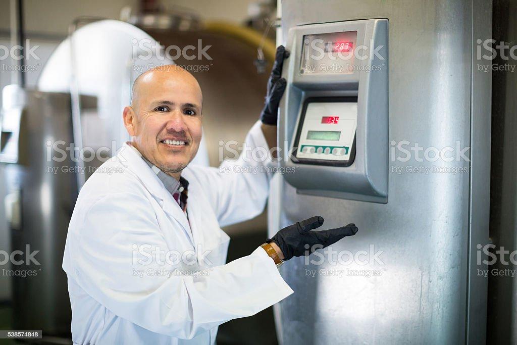 Portrait of worker near cisterns with milk stock photo