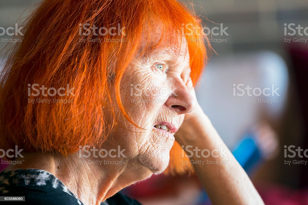 Portrait of worried redhead senior woman stock photo