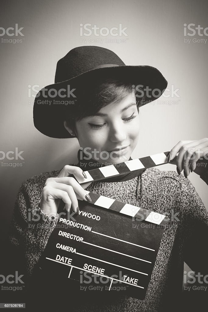 Portrait of young actress holding a movie clapper stock photo