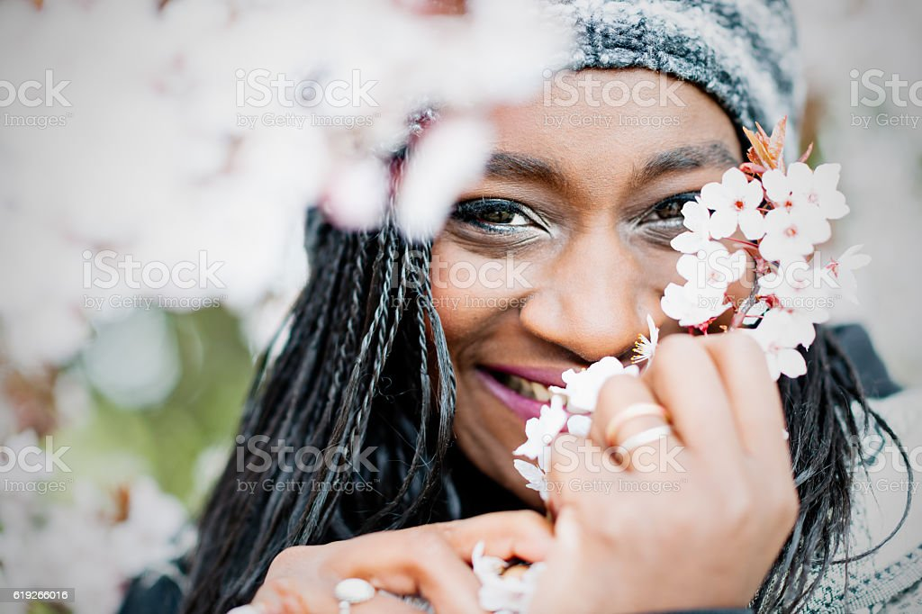 Portrait of young African woman with cherry blossoms stock photo