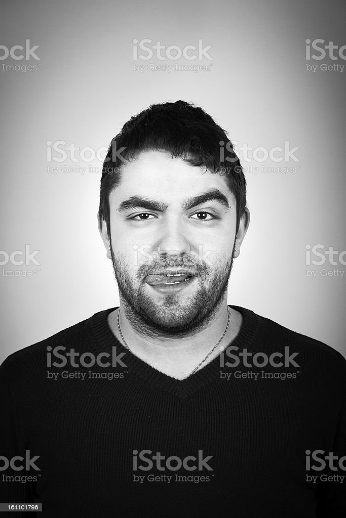 Portrait Of Young Arrogant Man With Tongue Out stock photo