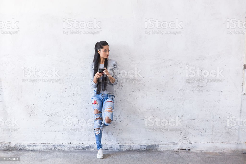 Portrait of young asian woman leaning back on blank wall stock photo