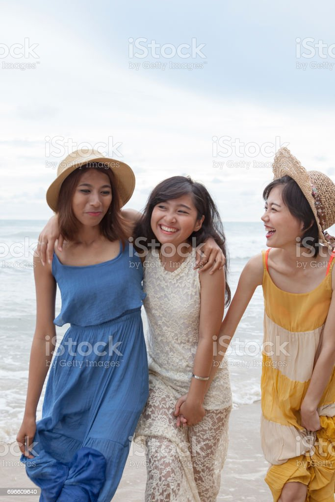 portrait of young asian woman with happiness emotion wearing beautiful dress walking on sea beach and laughing stock photo