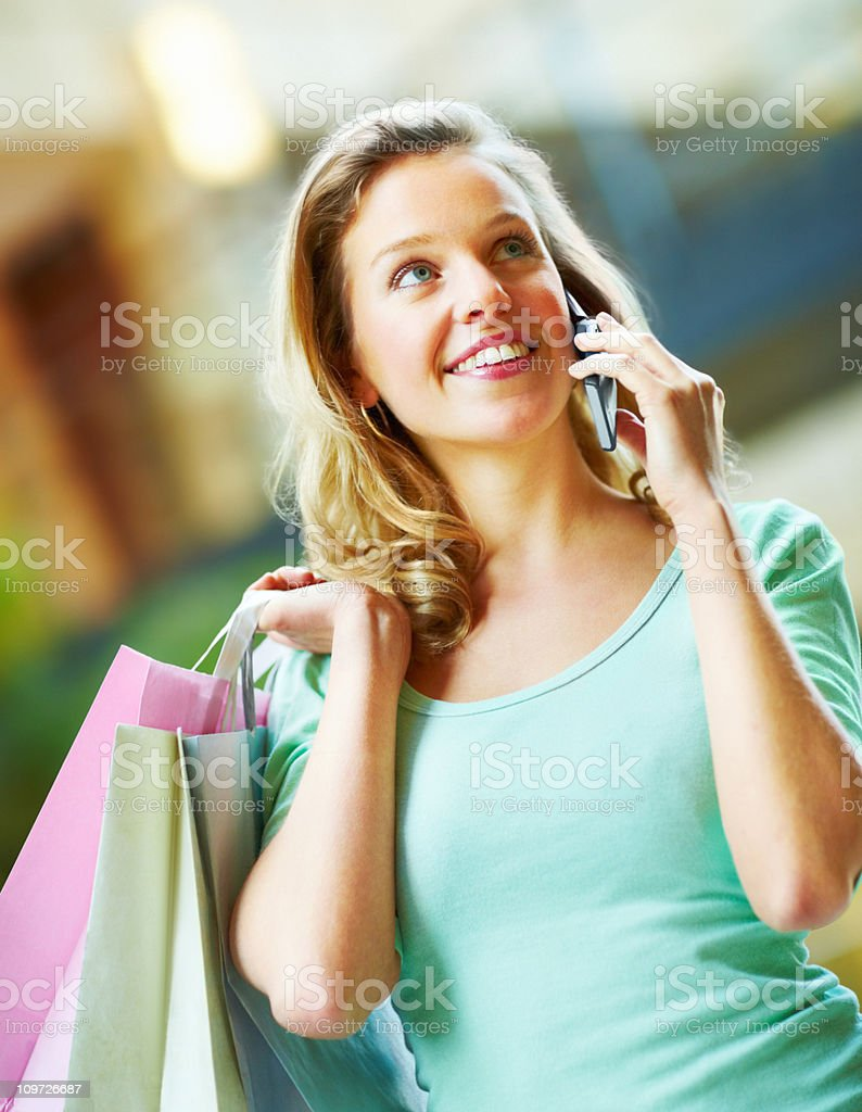 Portrait of young attractive female carrying bag holding cellphone royalty-free stock photo