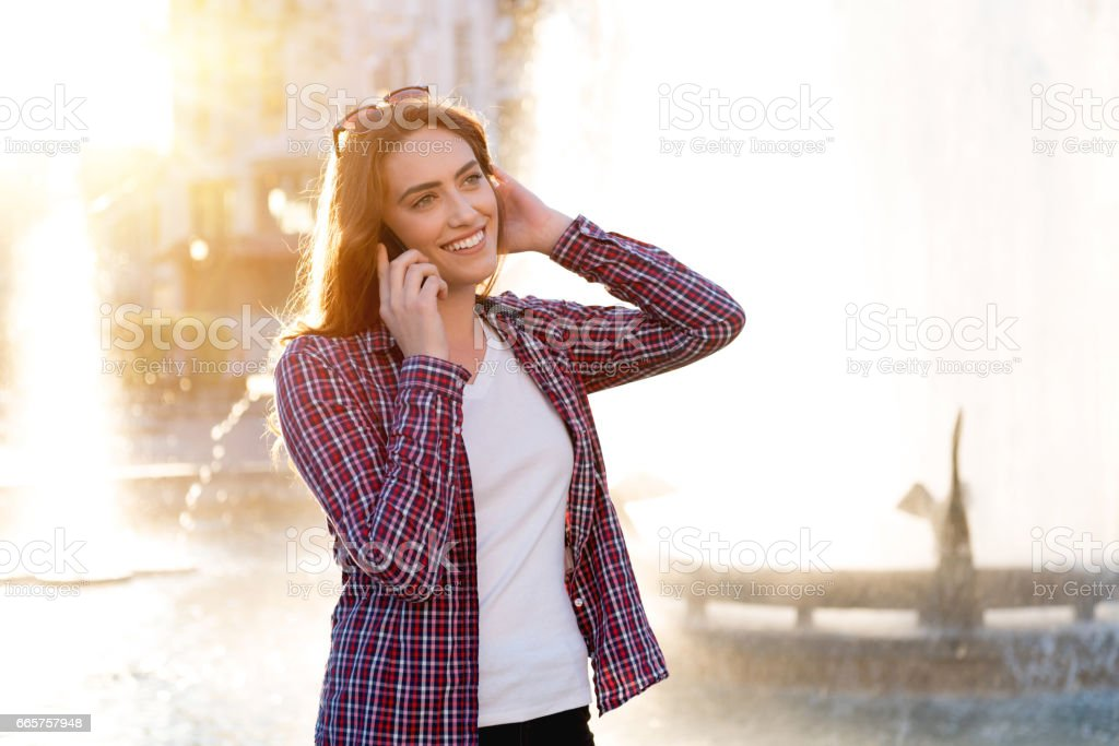Portrait of young attractive student outsides, talking on her phone stock photo