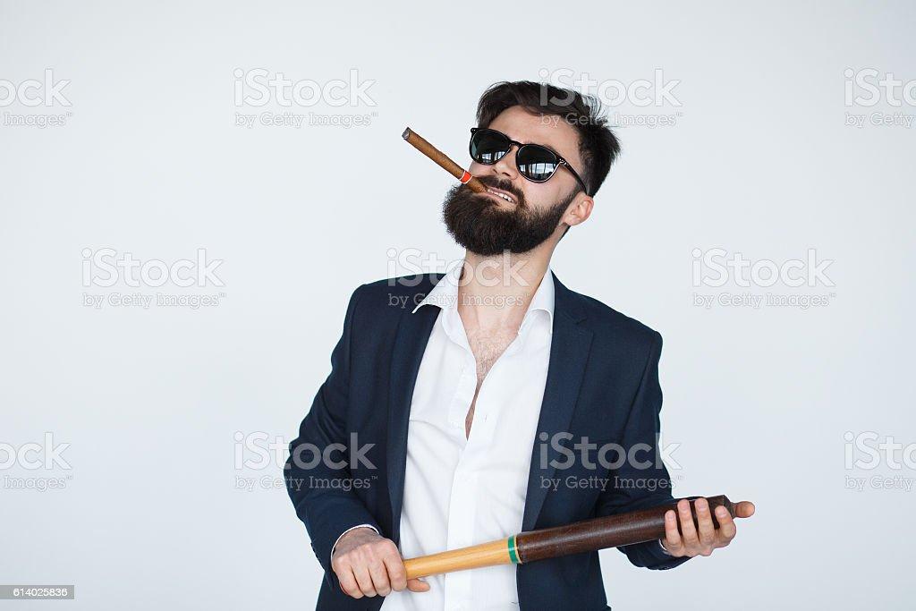 Portrait Of Young bearded man Holding Baseball Bat Over grey stock photo