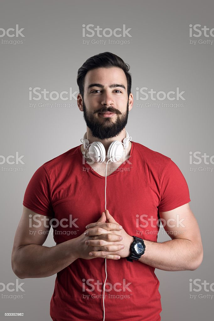 Portrait of young bearded man in red shirt with headphones stock photo