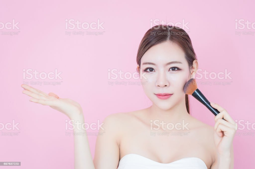 Portrait of young beautiful asian woman applying cosmetic brush powder. Smile girl showing empty copy space presenting your product on pink background stock photo