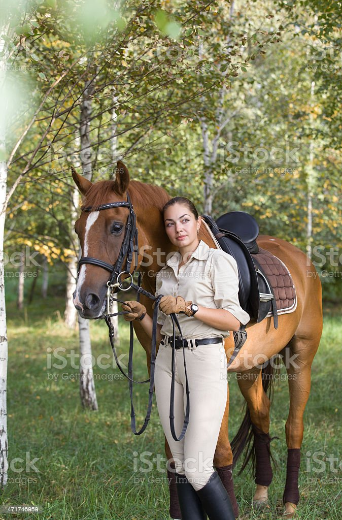Portrait of young beautiful brunette woman with a brown horse royalty-free stock photo