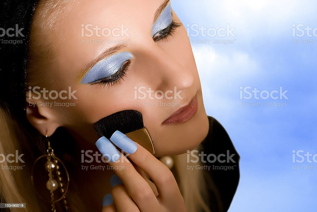 Portrait of young beautiful girl with brush on sky background royalty-free stock photo