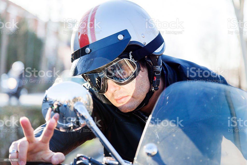 portrait of young biker riding his motorcycle stock photo