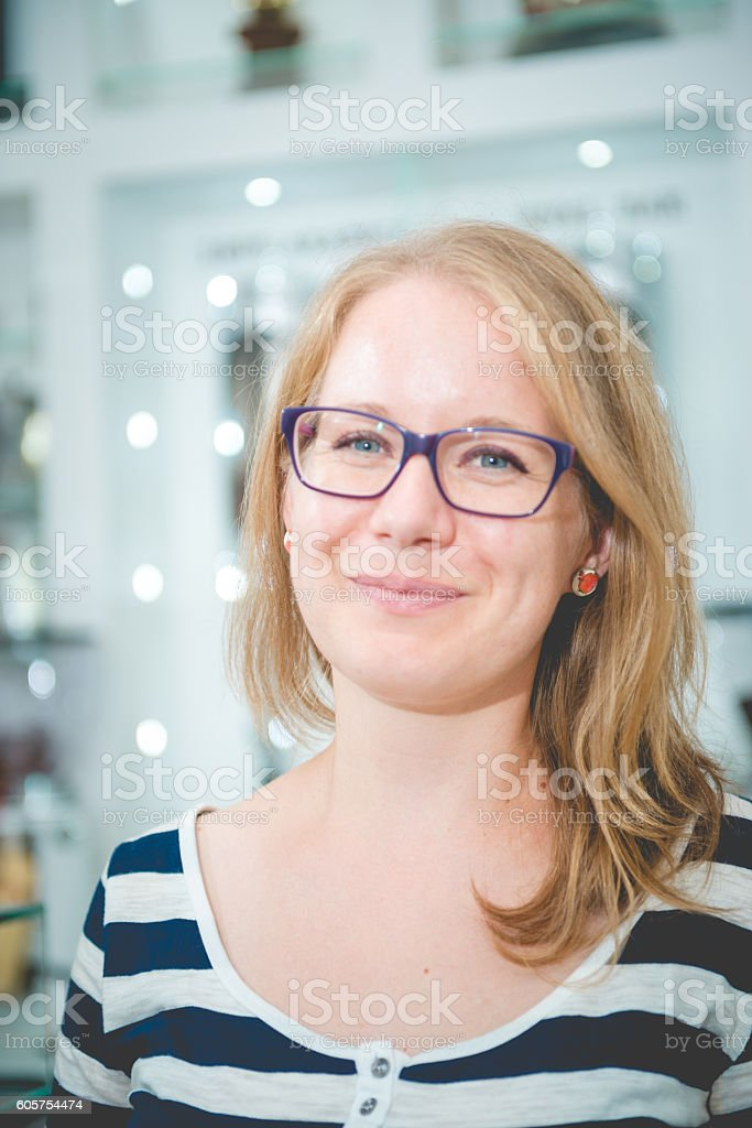 Portrait of Young Blond Woman with Eyeglasses in Cafe, Slovenia stock photo