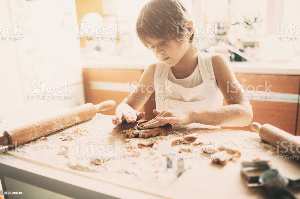 Portrait of young boy cutting dough stock photo