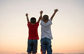 Portrait of young boys arms outstretched in nature
