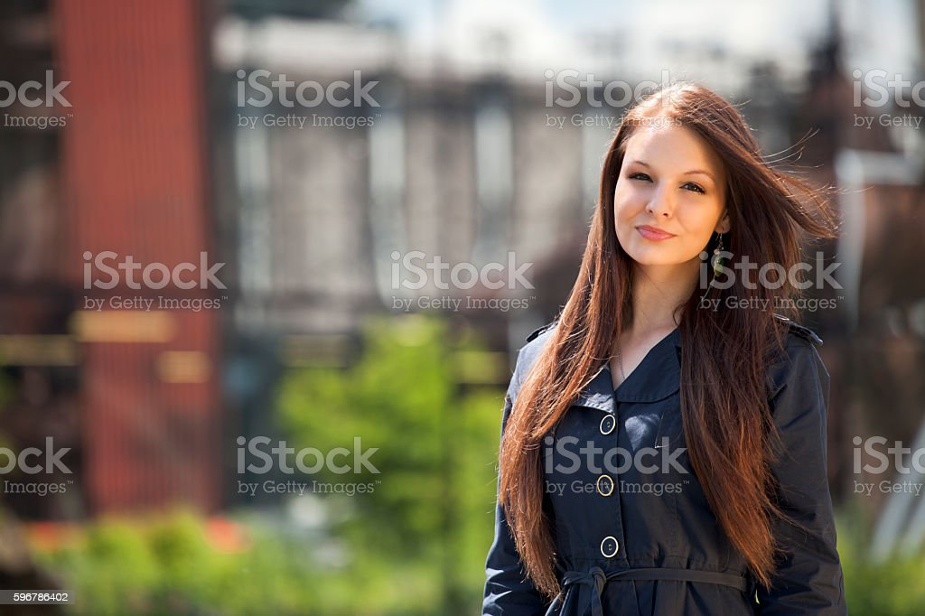 Portrait of young brunette woman in front of industry background stock photo