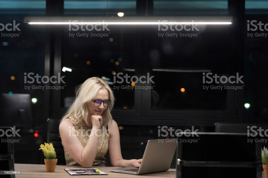 Portrait of young business woman in office at night stock photo