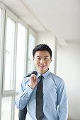 Portrait of young businessman in corridor