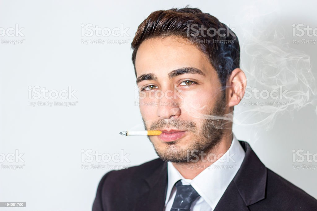 Portrait of young businessman smoking against gray background stock photo